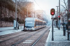 Modern subway train outdoors at stop. Outdoor metro or tram stop, two railway tracks, sidewalk of pavement stone, red traffic light and modern curved train with Royalty Free Stock Image