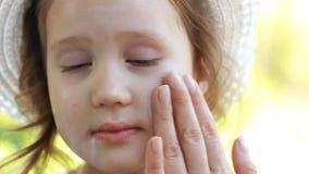 Modern suddar kräm för barnframsidasolen solbr?nna suncream Solskyddskr?m Closeupen behandla som ett barn flickan arkivfilmer