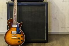 Modern sunburst electric guitar standing in front of amplifier, professional music equipment background stock image