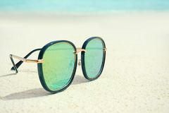 Modern sunglasses on beach sand. Summer vacation concept Royalty Free Stock Image