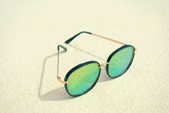 Modern sunglasses on beach sand. Summer vacation concept Royalty Free Stock Images