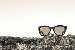 Modern sunglasses from beige plastic are located separately. Modern sunglasses from plastic of beige color are separately on a stone closeup against the empty Royalty Free Stock Images