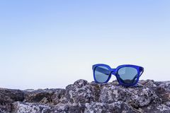 Modern sunglasses from blue plastic are located separately. On a stone against the blue sky a closeup Royalty Free Stock Photos