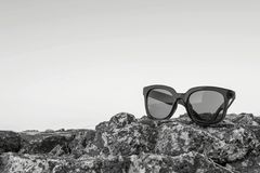 Modern sunglasses from monochrome plastic are located separately. Modern sunglasses from plastic of monochrome color are separately on a stone closeup against Royalty Free Stock Photos