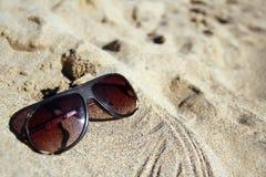 Modern sunglasses on sand Stock Images