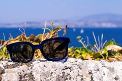 Modern sunglasses for sight closeup are located separately. Modern sunglasses for sight are located separately on a stone against a landscape a closeup Stock Photos