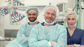 Surgical team poses at the surgery room. Modern surgical team posing at the surgery room. Senior male doctor standing against background of two his colleagues Royalty Free Stock Images