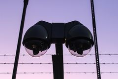 Modern surveillance camera and barbed wire royalty free stock image