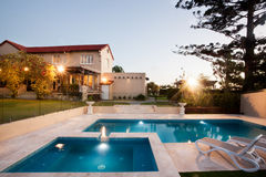 Modern swimming pool area with lights from a mansion Stock Images