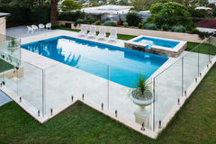 Modern swimming pool covered with glass panels beside a lawn stock photo