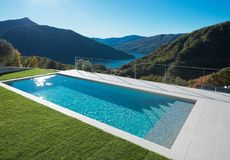 Modern swimming pool in the garden with lake and valley view Royalty Free Stock Image