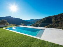 Modern swimming pool in the garden with lake and valley view Stock Image