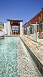 Modern swimming pool with outdoor patio area and wooden pillars Royalty Free Stock Photos