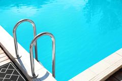 Modern swimming pool with step ladder. Outdoors stock photography