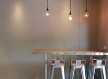 Modern table counter bar with chairs loft interior with gray tile wall and hanging decor lamps royalty free stock image