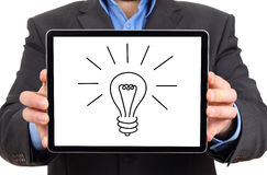 Tablet with bulb icon ,on male hands. Royalty Free Stock Photography
