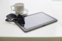 Modern tablet with coffee cup on white background Stock Photos