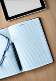 Modern tablet PC next to a classical open agenda Royalty Free Stock Image