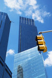 Modern tall office buildings. Modern blue office buildings with yellow traffic light in the foreground. Blue sky in the background Royalty Free Stock Photo
