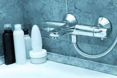 The modern tap in bathroom. And shampoos at a background Royalty Free Stock Images