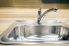 Modern tap faucet and sink on new kitchen Stock Image