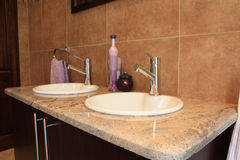 Modern taps. On a granite stone counter and purple decorations Stock Photos