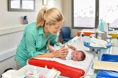 Modern tar att bry sig av hennes nyfött behandla som ett barn i barnbördshuset bada först royaltyfri bild