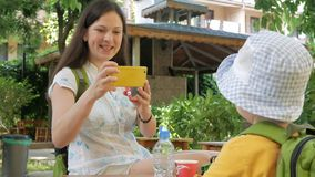 Modern tar en bild av en gullig unge i trädgården på telefonen Den unga kvinnan gör något foto på en gul smartphone stock video