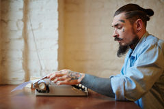 Modern Tattooed Writer with Old Typing Machine Royalty Free Stock Image