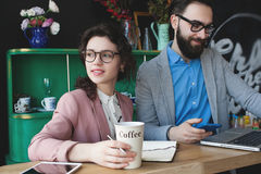 Modern team working in cafe with laptop, smartphone with coffee. Young hipster men with women in glasses collaborating in cafe using laptop, tablet, smartphone Royalty Free Stock Photos
