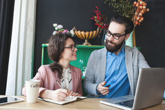 Modern team working in cafe with laptop, smartphone with coffee. Young hipster men with women in glasses collaborating in cafe using laptop, tablet, smartphone Stock Photos