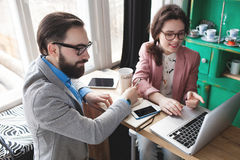 Modern team working in cafe with laptop, smartphone with coffee. Young hipster men with women in glasses collaborating in cafe using laptop, tablet, smartphone Royalty Free Stock Photo