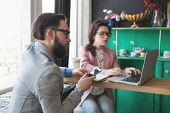 Modern team working in cafe with laptop, smartphone with coffee Royalty Free Stock Images