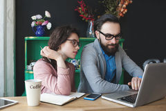 Modern team working in cafe with laptop, smartphone with coffee. Young hipster men with women in glasses collaborating in cafe using laptop, tablet, smartphone Stock Photo