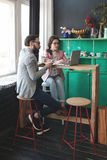Modern team working in cafe with laptop, smartphone with coffee. Young hipster men with women in glasses collaborating in cafe using laptop, tablet, smartphone Royalty Free Stock Image