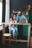 Modern team working in cafe with laptop, smartphone with coffee. Young hipster men with women in glasses collaborating in cafe using laptop, tablet, smartphone Stock Image