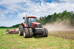 Modern tech red tractor plowing a green agricultural field in spring on the farm. Harvester sowing wheat. Stock Images