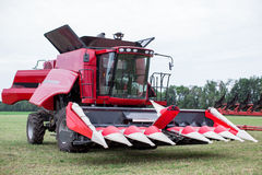 Modern tech red tractor plowing a green agricultural field in spring on the farm. Harvester sowing wheat. Stock Photos