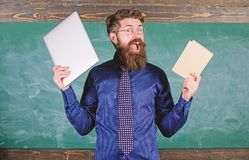 Modern technologies benefit. Stay modern with technology. Teacher bearded hipster holds book and laptop. Teacher. Choosing modern teaching approach. Digital stock photos