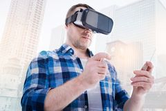 Bristled man in VR headset looking at transparent tablet. Modern technologies. Handsome middle-aged man wearing a VR headset and looking through it at a Royalty Free Stock Photo