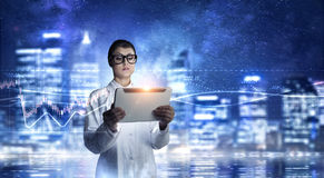 Modern technologies for medicine . Mixed media. Young and professional medical doctor using tablet pc Stock Image