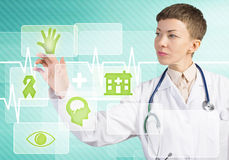 Modern technologies in medicine. Young female doctor touching icon of media screen Stock Photography