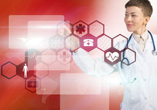 Modern technologies in medicine. Young female doctor touching icon of media screen Royalty Free Stock Photo