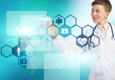 Modern technologies in medicine. Young female doctor touching icon of media screen Stock Photo