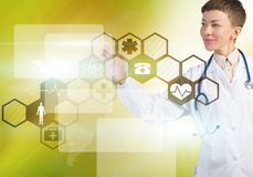 Modern technologies in medicine. Young female doctor touching icon of media screen Royalty Free Stock Photography