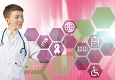 Modern technologies in medicine. Young female doctor touching icon of media screen Stock Images