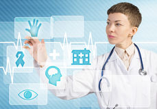 Modern technologies in medicine. Young female doctor touching icon of media screen Royalty Free Stock Image