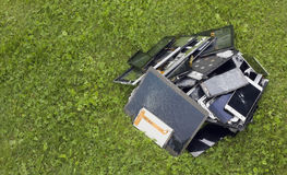 Modern technologies pollute environment copncept. Big heap of the  broken and cracked  cellular telephons and  tablets lie on green lawn grass. Modern Stock Photography