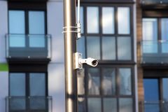 Modern technologies in video surveillance. Outdoor surveillance camera with Wi-Fi transmitter white, fixed on a pole on a house stock photos