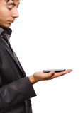 Modern technologies. Young businessman in dark grey coat standing isolated on white background with mobile phone in hand Royalty Free Stock Photos